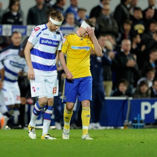 QPR's Kaspars Gorkss and Derby's Steve Davies nurse their wounds.