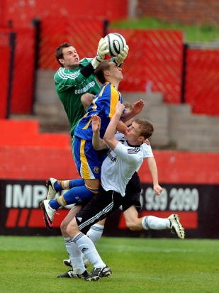 Derby County's goalkeeper Ross Atkins reaches for the ball during a game against Shrewsbury Town.